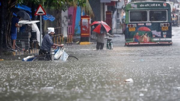 People wade through a waterlogged road after heavy rainfall in Mumbai. (REUTERS)