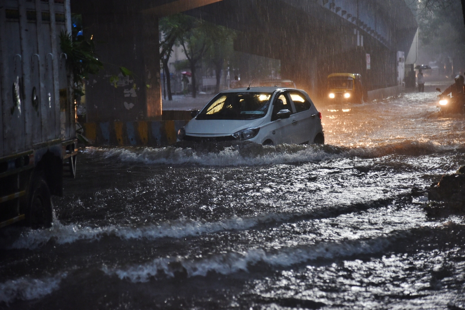 A car tries to don the cap of a boat as it attempts to negotiate a submerged road in Thane.