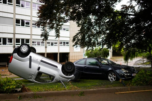 A damaged car lays on its roof on the roadside after flooding in Ensival, Verviers, Belgium. (AP)