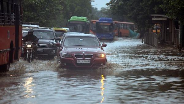 Commuters crossing a waterlogged stretch along Mathura Road during heavy rain in New Delhi. (Raj K Raj / HT Photo)