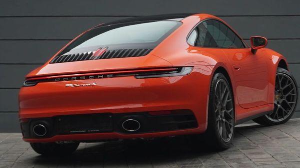 A Porsche 911 Carrera S Coupe in customized Lava Orange shade.