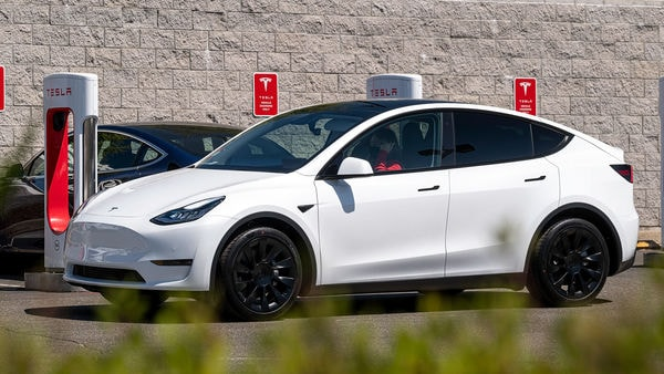 A Tesla electric vehicle drives past charging stations in US. (File photo) (Bloomberg)
