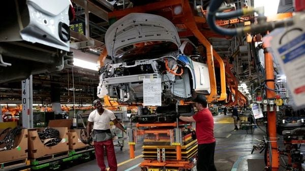 General Motors assembly workers connect a battery pack underneath a partially assembled Chevrolet Bolt EV vehicle on the assembly line. (File Photo) (REUTERS)