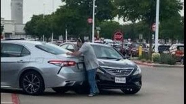 The driver of the Hyundai car tries to save his vehicle despite facing the risk of being in injured. (Image source: Screenshot of a video posted on YouTube by ViralHog)