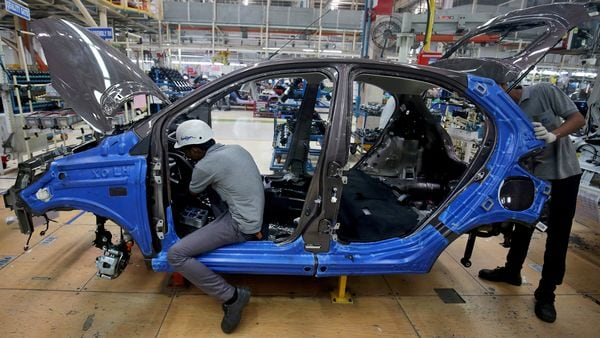 FILE PHOTO: Workers assemble a Tata Tiago car inside the Tata Motors car plant in Sanand, on the outskirts of Ahmedabad. (REUTERS)