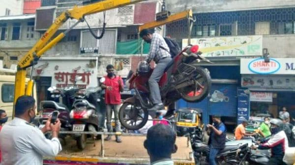 Motorcycle being towed along with the rider in Pune.