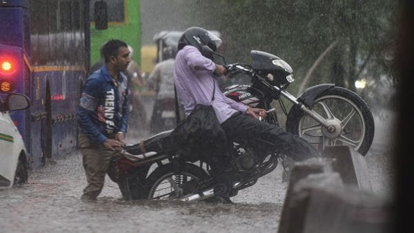 A motorist tries his best to get to safer ground in order to seek a clearer passage on water-logged roads. (Sanchit Khanna/HT PHOTO)