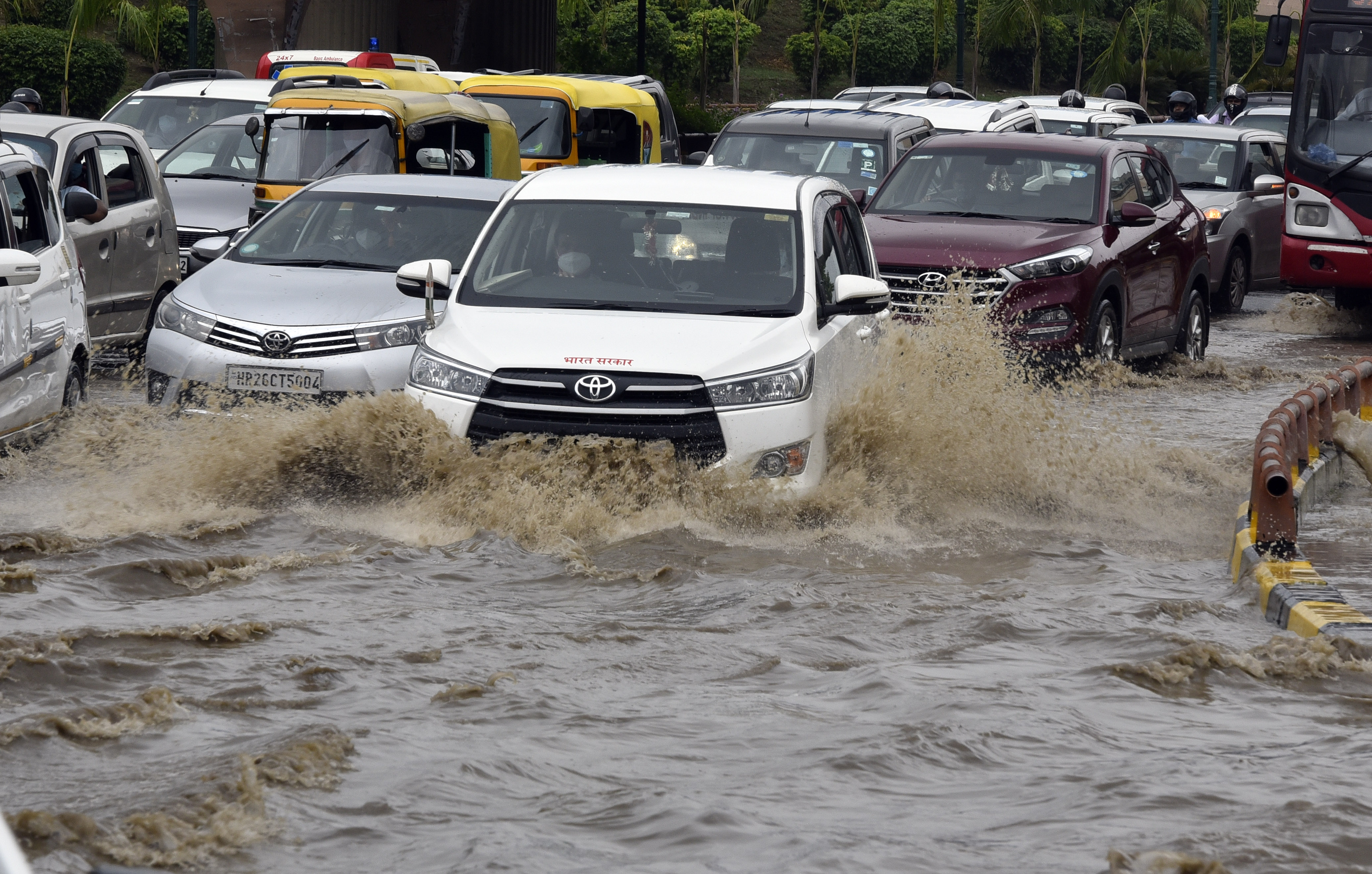 Vehicles wade through a water logged stretch after heavy rains at AIIMS in New Delhi. (Sanjeev Verma/HT PHOTO)