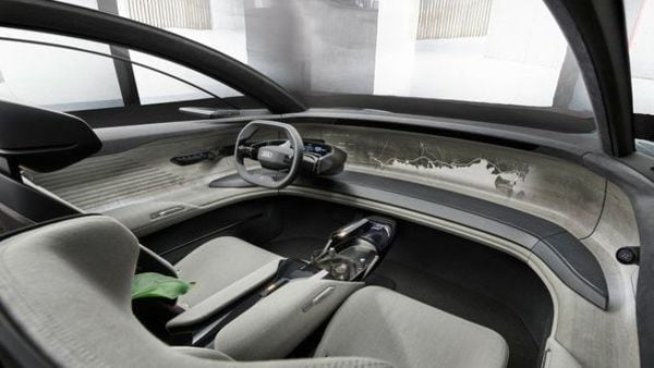 With large portal doors, Audi in the Grandsphere's interior has replaced the traditional blackened touch screen with one designed on a wooden subframe that surrounds the vehicle from door to door. The wheel and control functions are hidden behind a hinged dash panel and appear only at the driver's command. (Audi)