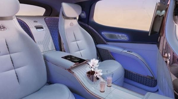 Mercedes-Benz has created a floating centre console in the rear of the Maybach electric vehicle and has also provided enough space for free movement. The rear section sports white piano lacquer and rose gold-coloured accents while there is a Deep-Sea Blue shade on other materials here. Faux fur has been used to wrap the flooring.