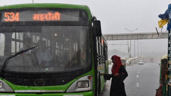 File photo: A woman getting on to a DTC bus while it rains on a National Highway near Pandav Nagar in New Delhi, India, (Ajay Aggarwal /HT PHOTO)