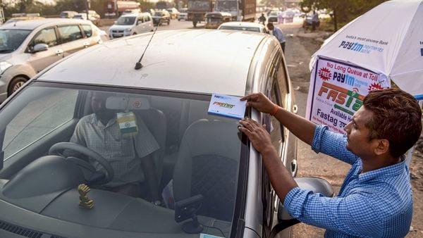 A worker fixes a FASTag sticker on the windscreen of a car. (File photo used for representational purpose only) (PTI)
