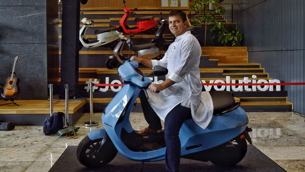 Bhavish Aggarwal, Co-founder and CEO of Ola, poses for a photograph with the new Ola electric scooter during its launch at the Ola headquarters in Bangalore on August 15, 2021. (AFP)