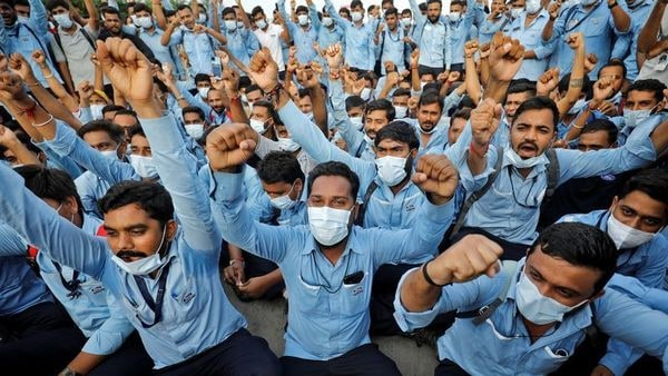 Workers of Ford Motor Co. shout slogans during a protest outside Ford's car assembly and engine-making facility in Sanand, Gujarat, India, September 21, 2021. (REUTERS)