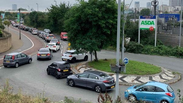 An aerial view shows customers queueing in their cars to access an Asda petrol station in east London on September 25, 2021. (AFP)