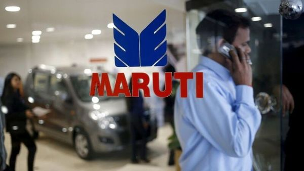 FILE PHOTO: A man speaks on his mobile phone as he exits a glass door with the logo of Maruti Suzuki India Limited at a showroom in New Delhi, India. (REUTERS)