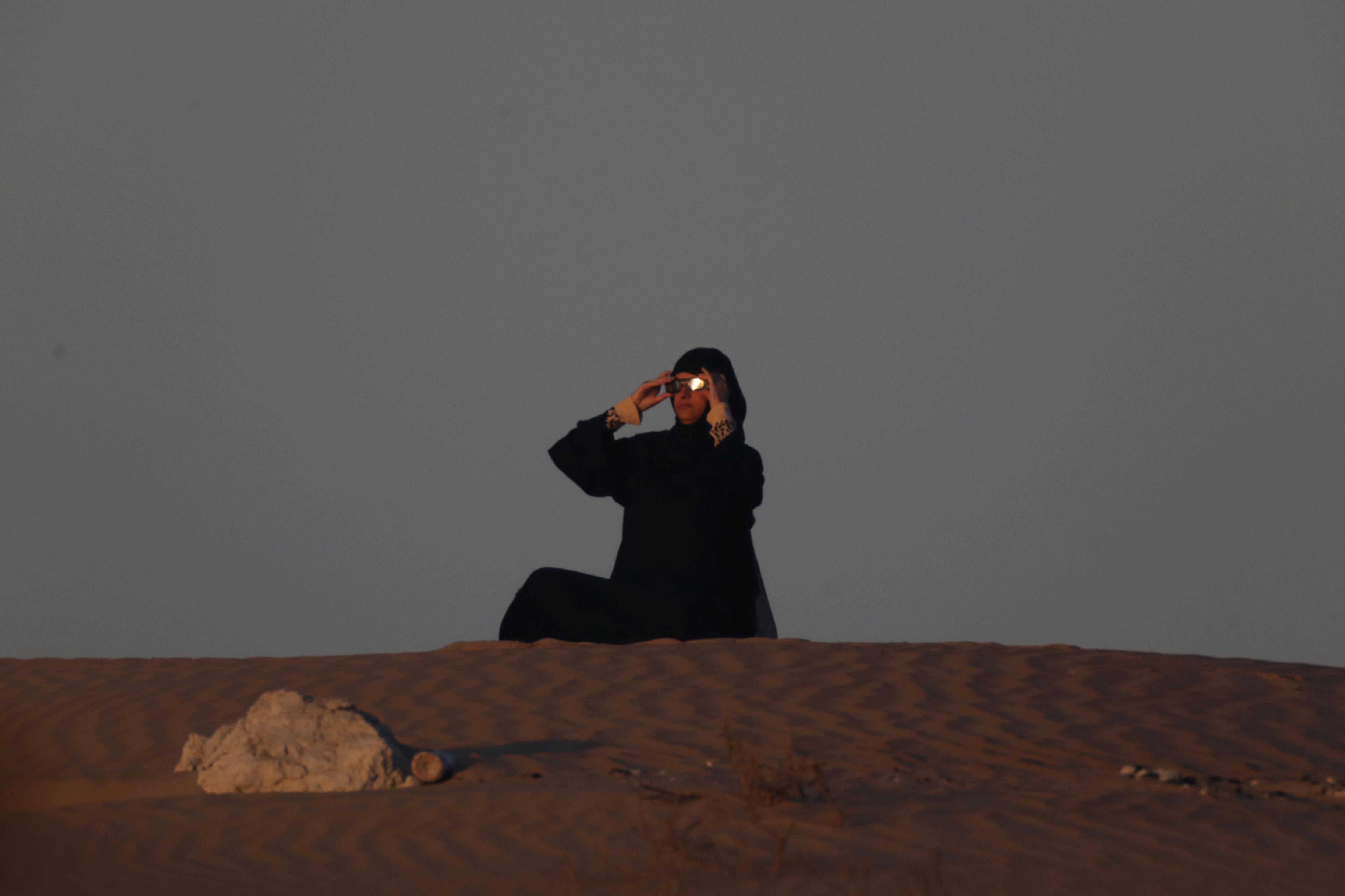 আবুধাবি থেকে সূর্যগ্রহণ দেখছেন এমিরেটস নিবাসী এক মহিলা (REUTERS)