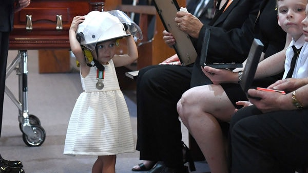 বুধবার অ্যান্ড্রুর স্মরণসভায় হাজির ছিলেন অস্ট্রেলিয়ার প্রধানমন্ত্রী স্কট মরিসন। সেখানেই বাবার হেলমেট মাথায় তুলে নিতে দেখা যায় অ্যান্ড্রুর ছোট্ট মেয়ে শার্লেটকে। (REUTERS)