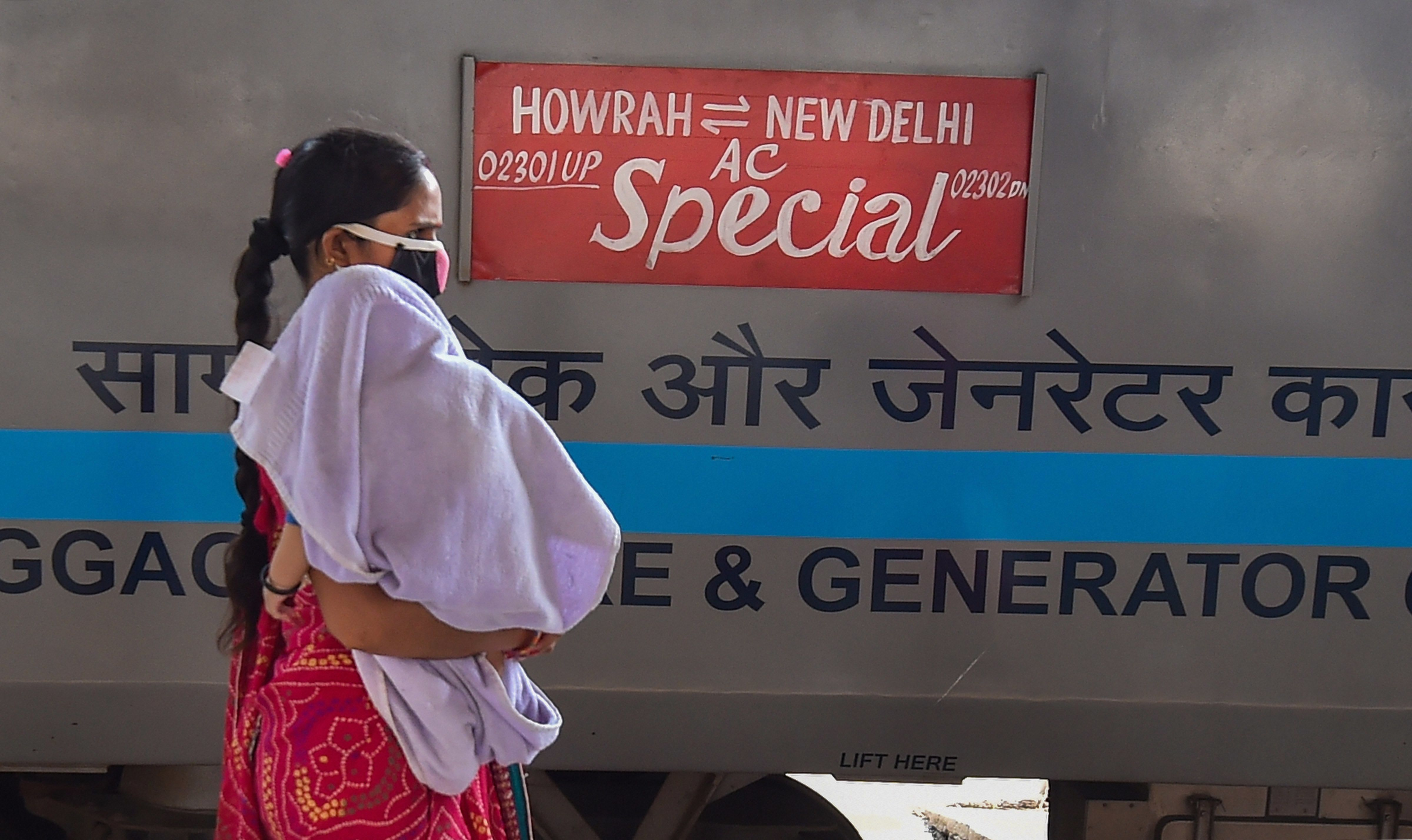 বাচ্চাকে নিয়ে এক মহিলা উঠছেন বিশেষ ট্রেনে (PTI)