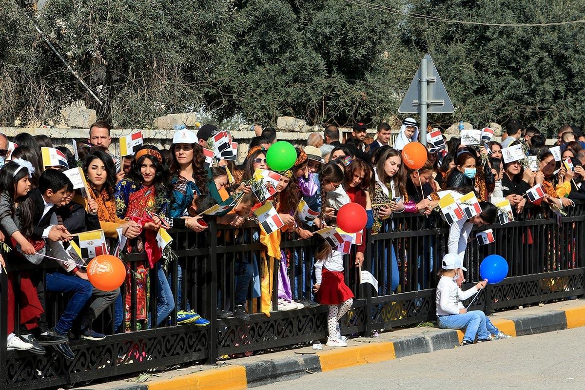 আজ সেই ধূসর ইরাক অনেক বেশি রঙিন। ইরাকের কারাকোশ-এ পোপের আগমনে রঙবেরঙের বেলুন, পোশাকে সেজেছে নগরবাসী। ছবি: আরি জালাল/রয়টার্স (Reuters) (Reuters)