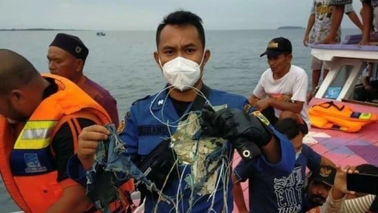 A member of the rescue team looking for an Indonesian plane that lost contact after taking off from the capital Jakarta holds suspected debris, at sea, January 9, 2021, in this picture obtained from social media. (@HUMASJAKFIRE via REUTERS)