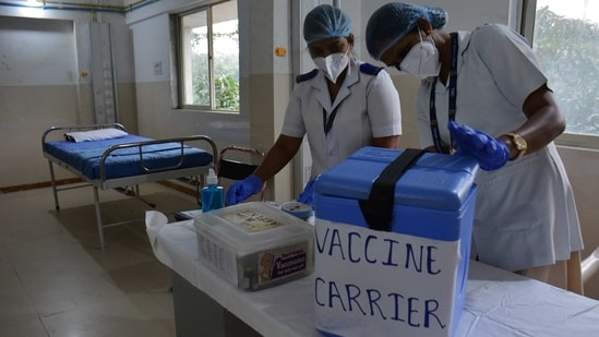 Health workers examine a vaccine carrier at Thane Municipal Corporation's Roja Gardenia Health Centre in Thane on January 8. The Directorate General of Civil Aviation (DGCA) also issued guidelines to all aircraft operators who plan to transport Covid-19 vaccines packed in dry ice to various parts of the country.(Praful Gangurde / HT Photo)