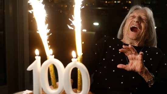 Agnes Keleti, former Olympic gold medal winning gymnast, reacts to fireworks going off on her birthday cake in Budapest.(AP)