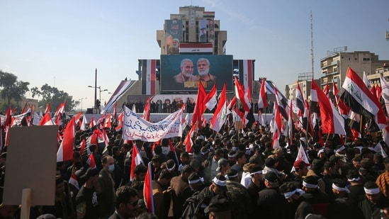 Iraqi demonstrators lift flags and placards as they rally in Tahrir square in the capital Baghdad on January 3, to mark one year after a US drone strike killed Iran's revered commander Qasem Soleimani (billboard L) and his Iraqi lieutenant Abu Mahdi al-Muhandis (billboard R) near the capital.(Ahmad Al-Rubaye / AFP)