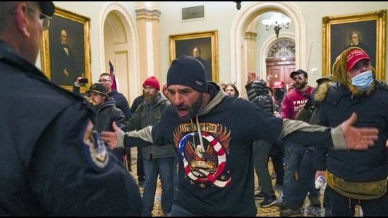 Trump supporters gesture to US Capitol Police in the hallway outside of the Senate chamber after breaching the halls of the Capitol in Washington, January 6, 2021 (AP)
