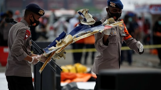 Indonesian police officers carry debris of Sriwijaya Air flight SJ 182, which crashed to the sea, at Tanjung Priok port in Jakarta, Indonesia,(Reuters)