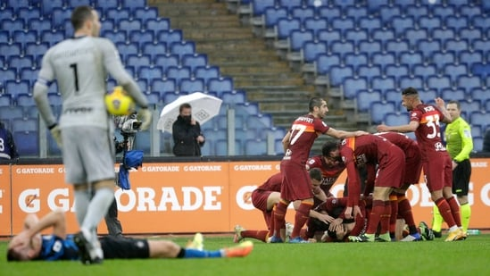 Roma's Gianluca Mancini is celebrated by teammates after he scored his side's second goal during a Serie A soccer match between Roma and Inter Milan at Rome's Olympic stadium,(AP)