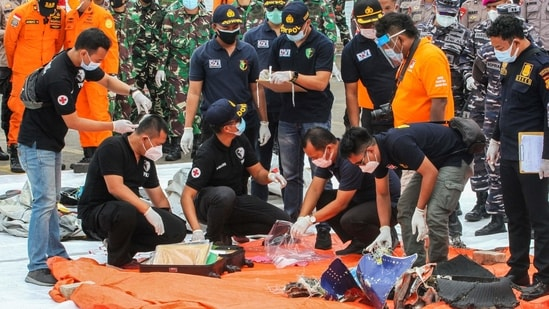 Rescue workers inspect recovered items and debris from the Sriwijaya Air Boeing 737-500 aircraft at the port in Jakarta on January 10. Indonesia detected signals on January 10 that could come from a flight recorder of the Sriwijaya Air jet that crashed into the sea soon after taking off from the capital Jakarta on January 9, as human body parts and suspected pieces of the plane were retrieved, Reuters reported.(Dany Krisnadhi / AFP)