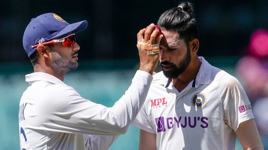 India's Mayank Agarwal, left, rubs the ball on the face of India's Mohammed Siraj during play on day four of the third cricket test between India and Australia at the Sydney Cricket Ground, Sydney, Australia, Sunday, Jan. 10, 2021. (AP)