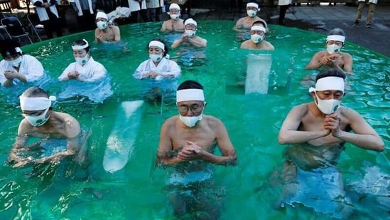 Participants wearing protective face masks amid the coronavirus disease (COVID-19) outbreak, pray as they take an ice-cold bath during a ceremony to purify their souls and to wish for overcoming the pandemic at the Teppozu Inari shrine in Tokyo, Japan, January 10, 2021. REUTERS/Kim Kyung-Hoon(REUTERS)