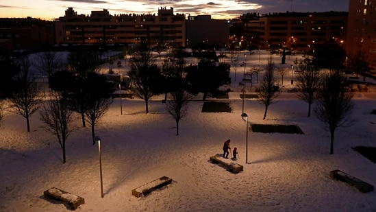 People using walking sticks to wade through the snow in Madrid on January 10. Most residents have heeded the government's call to stay at home, with the capital's streets all but deserted and quiet, except for the sound of shovels scraping snow and ice.(Susana Vera / HT Photo)
