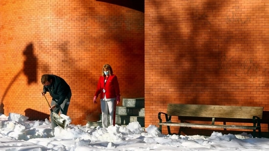 A worker shovels snow from the entrance of a building after heavy snowfall in Madrid on January 11. Throughout the weekend, people had been responding to calls to help clear vital paths in their neighbourhoods to allow access to hospitals and neighbourhood health centers.(Sergio Perez / REUTERS)
