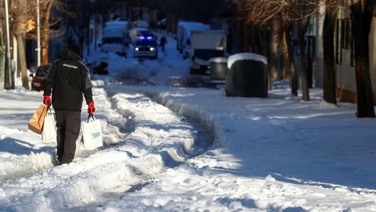 A person holding bags walks through a snow-covered street after heavy snowfall in Madrid on January 11. The Spanish government has insisted the travel chaos will not affect the distribution of the coronavirus vaccine, with 350,000 doses due to be rolled out nationwide on January 11.(Sergio Perez / REUTERS)