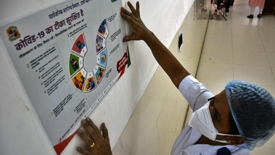 """A worker fixes a poster during a vaccination dry run at Thane Municipal Corporation's Roja Gardenia Health Center on January 8. The world's largest immunisation exercise against Covid-19, will kick off with priority to about 30 million healthcare and frontline workers. Prime Minister Narendra Modi has called it a """"a landmark step"""" in the fight against the pandemic.(Praful Gangurde / HT Photo)"""