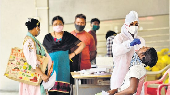 A health worker collects swab sample of a resident at Goregaon (West) in Mumbai on Monday. (Satyabrata Tripathy/ HT PHOTO)