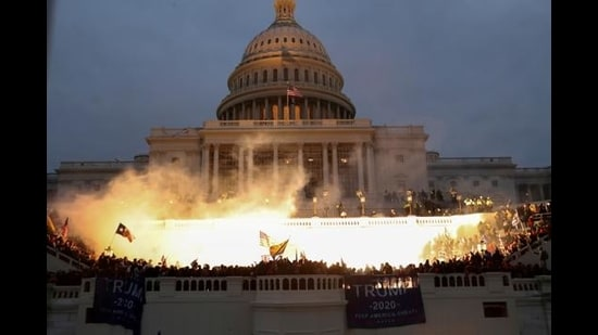 An explosion caused by a police munition is seen while supporters of US President Donald Trump gather in front of the US Capitol Building in Washington, January 6, 2021. (REUTERS)