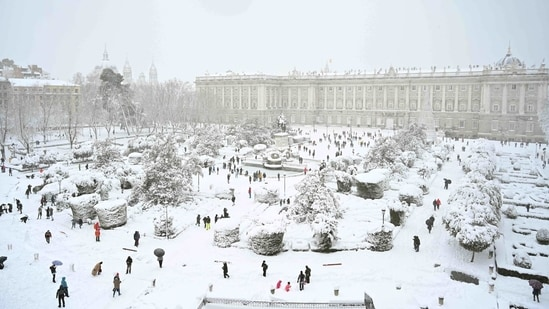 People out in the snow outside the Royal Palace in Madrid on January 9. In Madrid, authorities are calling on citizens to avoid using the few lanes that civil protection and military battalions, aided by snowplows and bulldozers, have managed to clear for ambulances and emergency vehicles.(Gabriel Bouys / AFP)