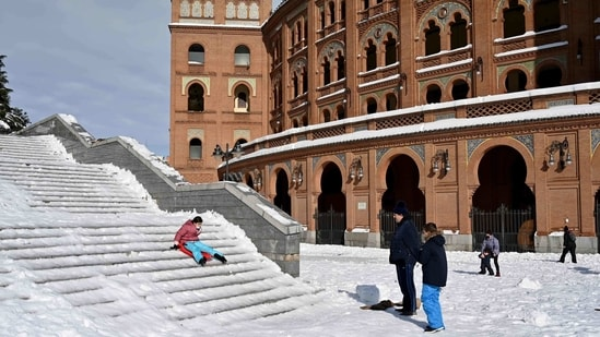 A woman slides down steps outside the Las Ventas bullring in Madrid on January 10. With a sharp drop in temperatures on January 11 and frost freezing much of the snow, which reached more than 50 centimeters in some urban areas, authorities are calling on people to avoid all but essential trips out of their homes.(Gabriel Bouys / AFP)