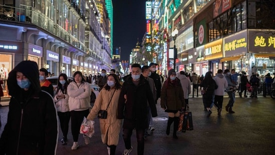 People wearing face masks walk on Jianghan street in Wuhan on January 10, 2021, the eve of the first anniversary of China confirming its first death from the Covid-19 coronavirus. (AFP)