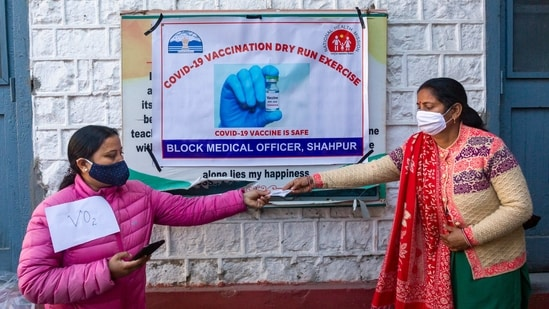 A health official asks for an ID from a volunteer during a mock vaccination drill in Dharamshala on January 11. More than 61,000 programme managers, 200,000 vaccinators and 370,000 other vaccination team members have been trained for the drive so far at state, district and block levels, according to the health ministry.(Ashwini Bhatia / AP)