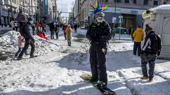 A man snowboards down the Gran Via avenue in downtown Madrid on January 10. Much of the city's main services remained closed on January 11, including the main wholesale market, although some supermarkets and newsstands opened for the first time in three days.(Manu Fernandez / AP)