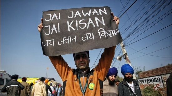 A farmer holds a placard during their ongoing protest against new farm laws, Singhu border, Delhi, January 10, 2020 (ANI)
