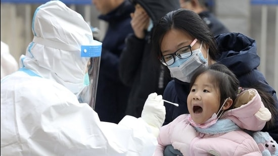 A health worker in a protective suit takes a swab from a child for a coronavirus test in Shijiazhuang in northern China's Hebei Province on January 12. (AP)