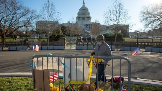 Sal Gonzalez places flowers at a memorial to honor slain Capitol Police Officer Brian Sicknick on the west side of the U.S. Capitol building on Capitol Hill in Washington, U.S., January 10, 2021. REUTERS/Allison Shelley(REUTERS)