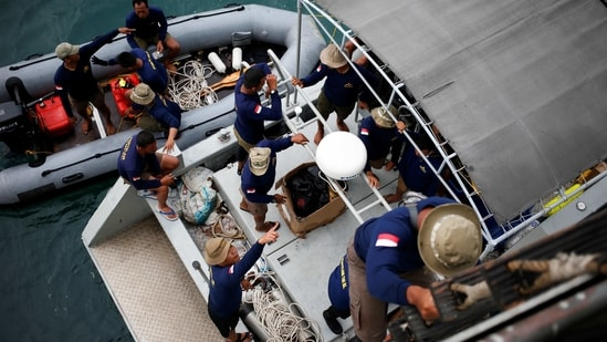 Indonesian navy divers are seen on a rubber boat and aboard the Indonesian Naval warship as they prepare to participate in the search and rescue operation for the Sriwijaya Air flight SJ 182, at the sea off the Jakarta coast, Indonesia, (Reuters)