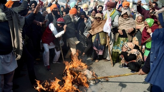 Farmers burn an effigy during a protest against farm bills at the Singhu Border in New Delhi on Monday. (ANI Photo)